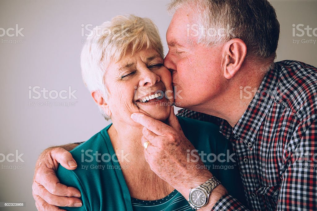 Senior man kissing wife on cheek stock photo