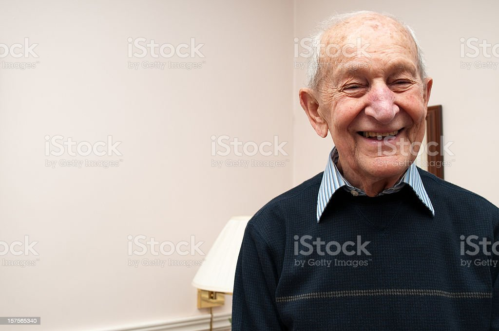 Senior man laughing standing up in his living room stock photo