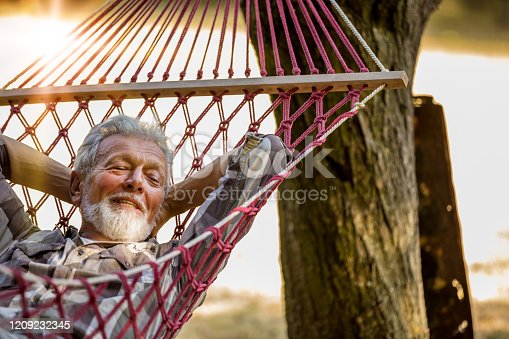 Senior caucasian man swinging in a hammock in a pleasant laziness of a weekend morning. He is smiling through his beard