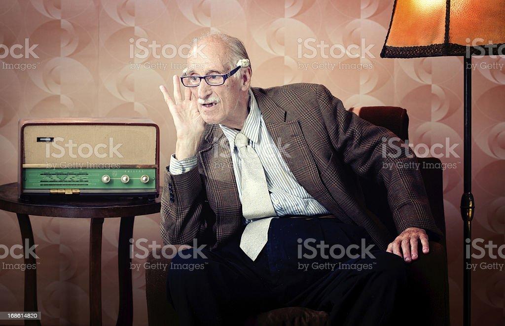 Senior man leaning in to listen to retro radio stock photo