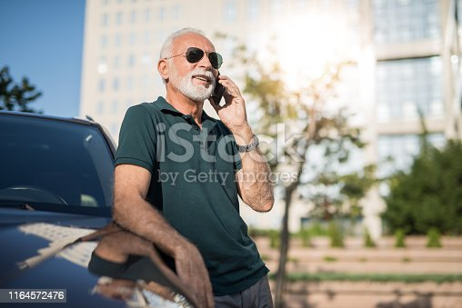 Senior man leaning on his car and having a phone conversation.