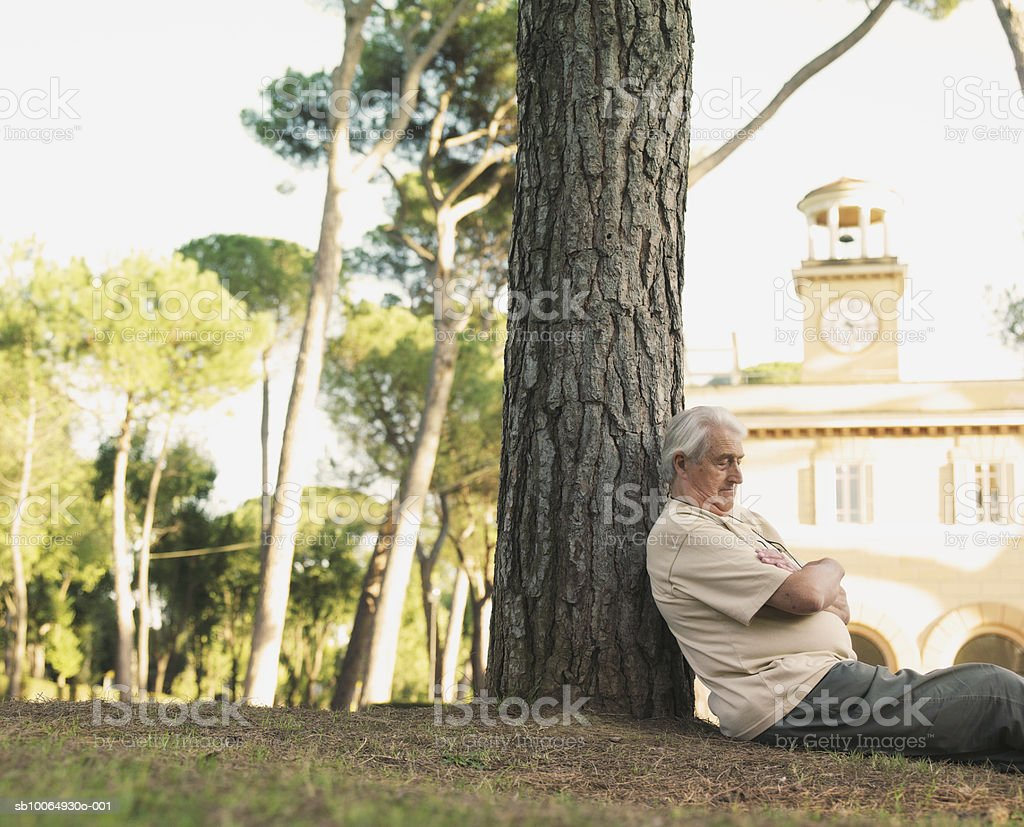 Senior man leaning on tree trunk, eyes closed foto royalty-free