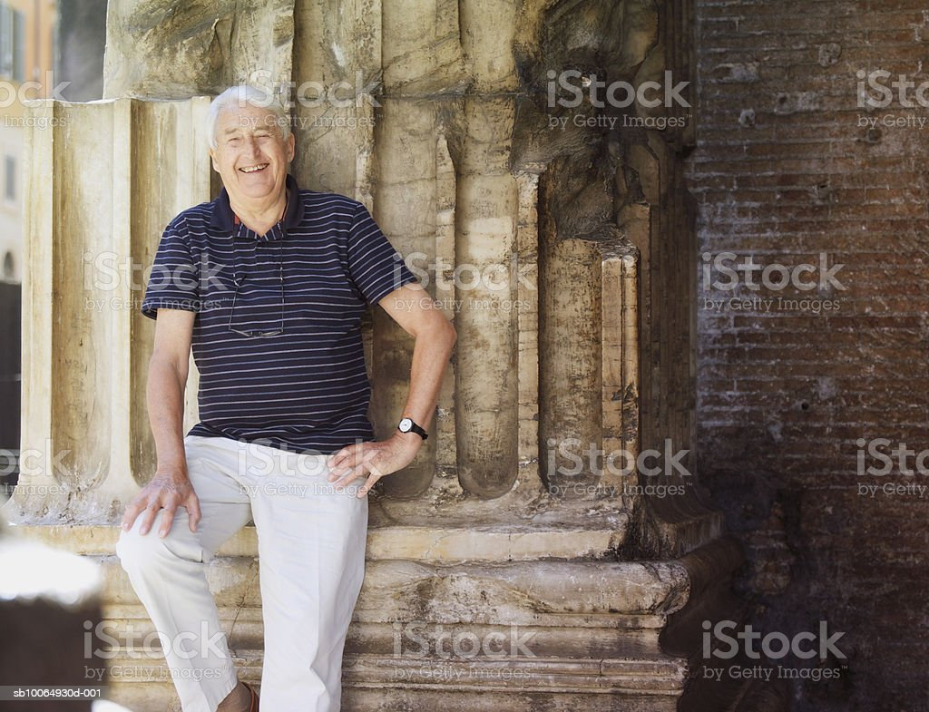 Senior man leaning on wall, smiling, portrait royalty-free stock photo