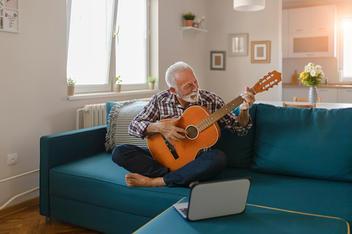 Senior Man Learns to Play Acoustic Guitar Online
