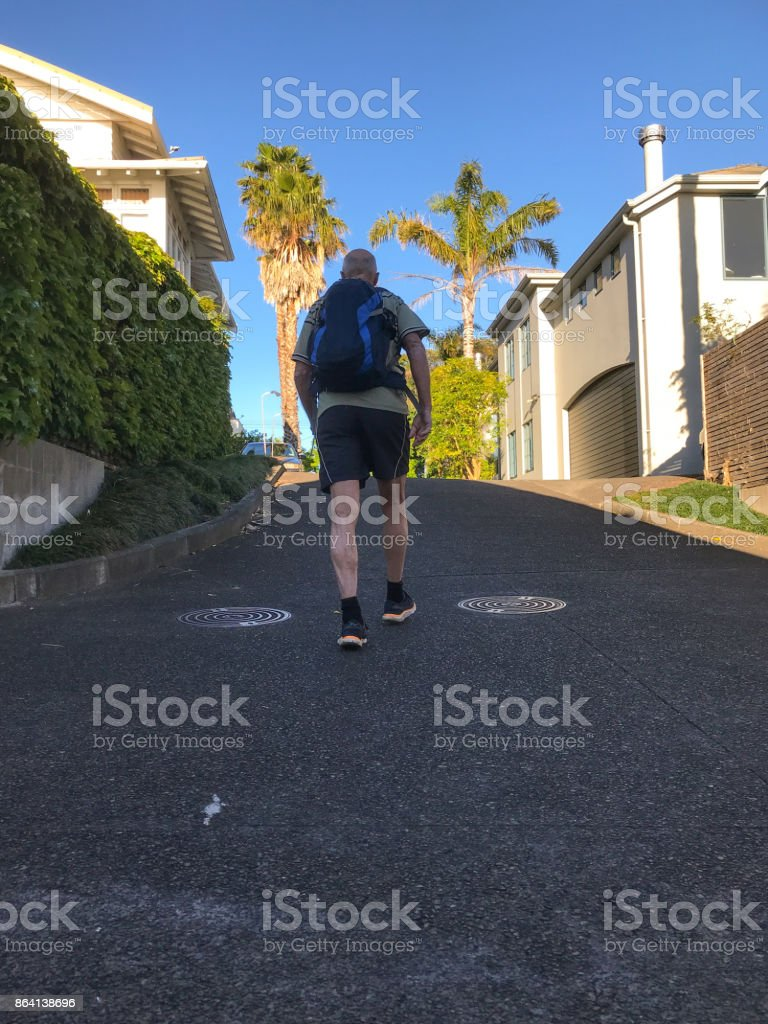 Senior man leaves home in the morning to walk to work in New Zealand royalty-free stock photo