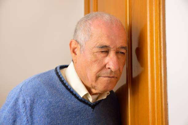 senior homme écoute derrière la porte - indiscret photos et images de collection
