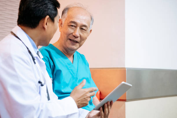 Senior man listening to doctor with tablet stock photo