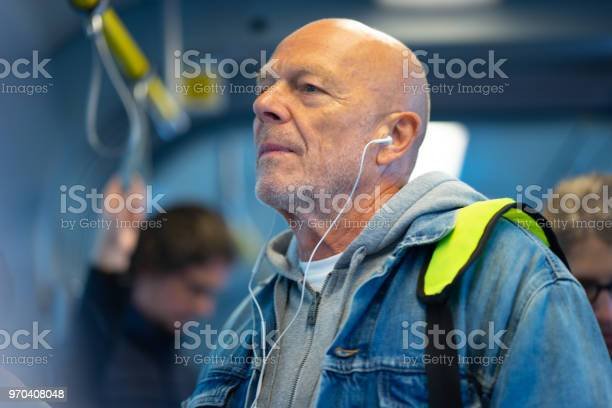 Senior man listening to earphones on public transport picture id970408048?b=1&k=6&m=970408048&s=612x612&h=cj3yopeciac 4up3immdodmlrkhndhfpchqrqvz3aog=