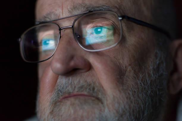 senior man looking at a computer screen - pensionati lavoratori foto e immagini stock