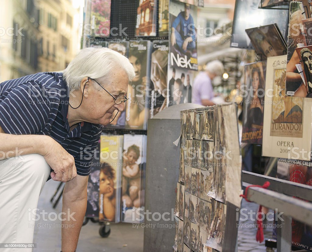 Senior man looking at books in street royalty free stockfoto