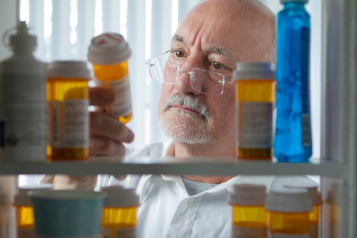 Senior man looking at prescription drugs