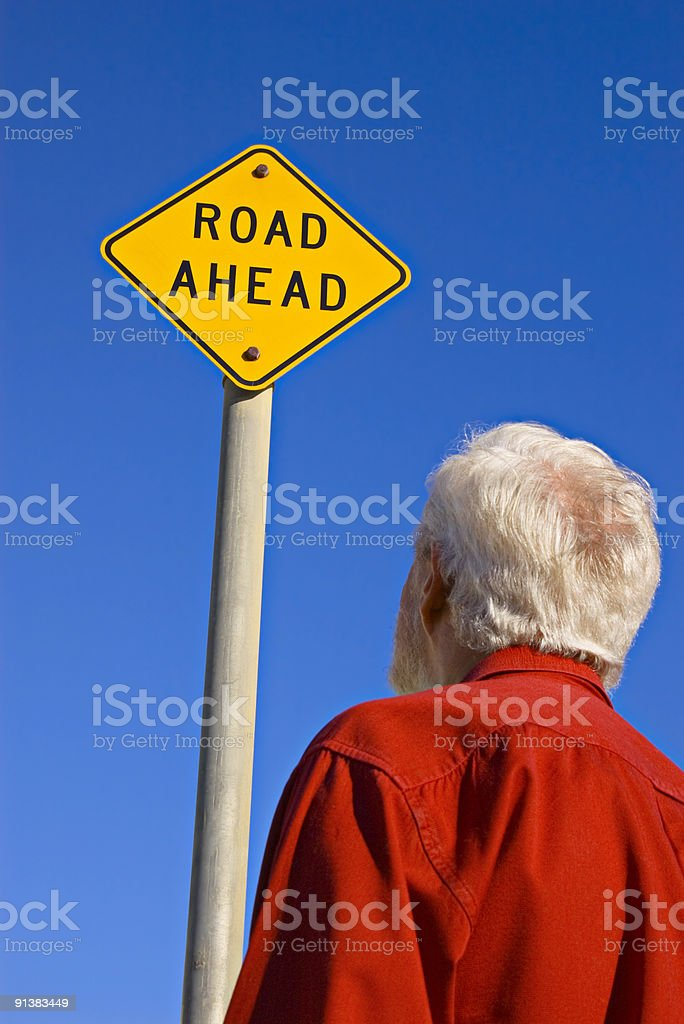 Senior Man Looking at  Sign which says Road Ahead royalty-free stock photo