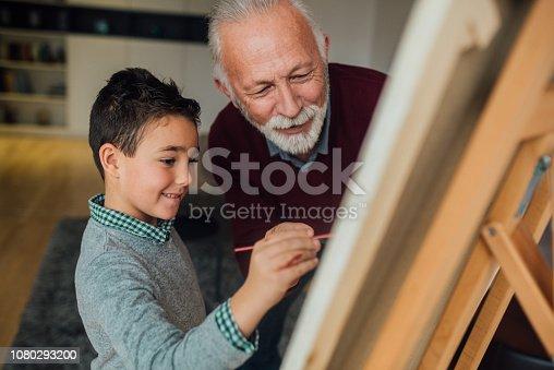 istock Senior man looking at young boy painting 1080293200