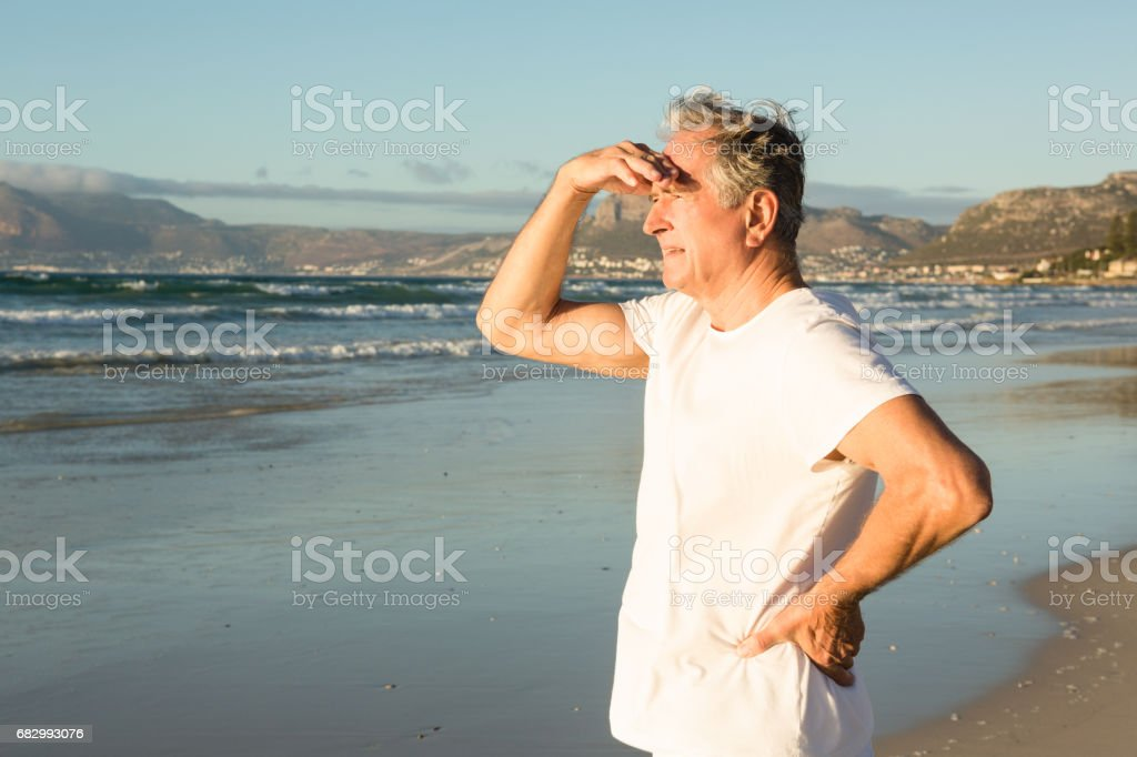 Senior man looking away while standing on shore royalty-free stock photo