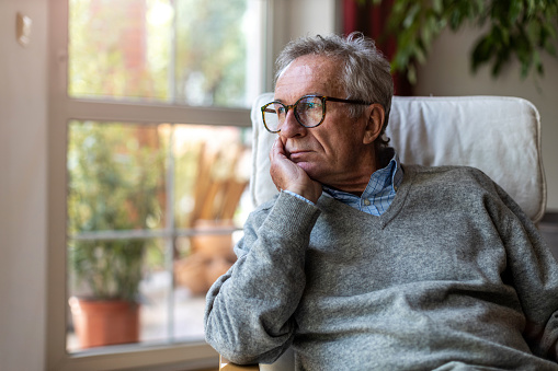 Senior man looking out of window at home