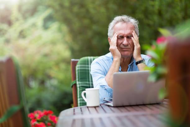 Senior Mann sieht gestresst, während der Arbeit auf Laptop – Foto