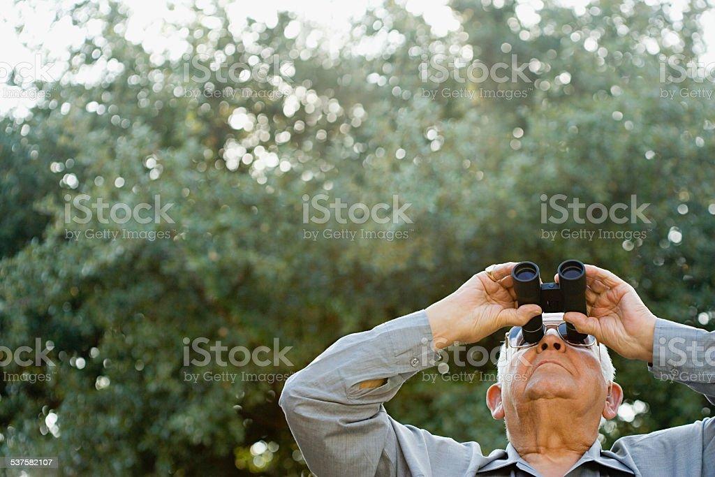Senior man looking through binoculars stock photo