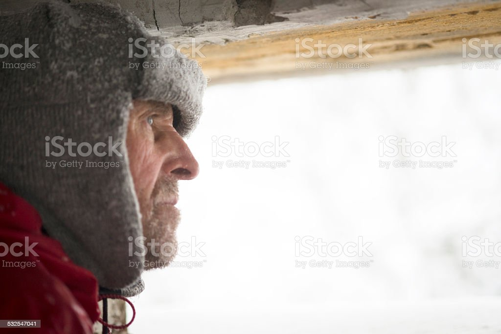 Senior Man Looking  through Great War's Bunker Porthole , Snowing, Europe stock photo