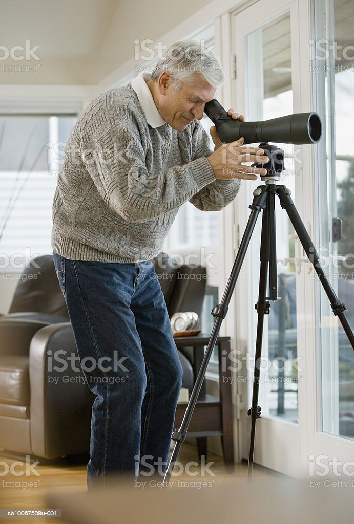 Senior man looking through telescope, side view foto de stock royalty-free