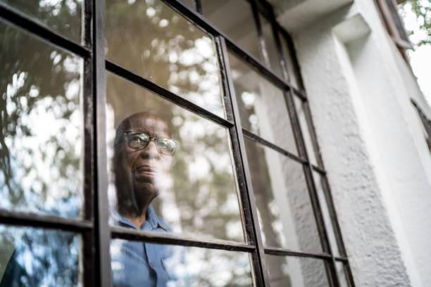 Senior man looking through the window at home stock photo