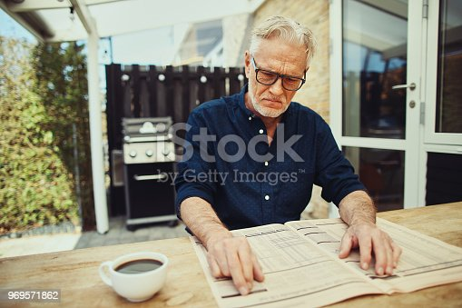 116379055 istock photo Senior man looking unhappy while reading a financial newspaper 969571862