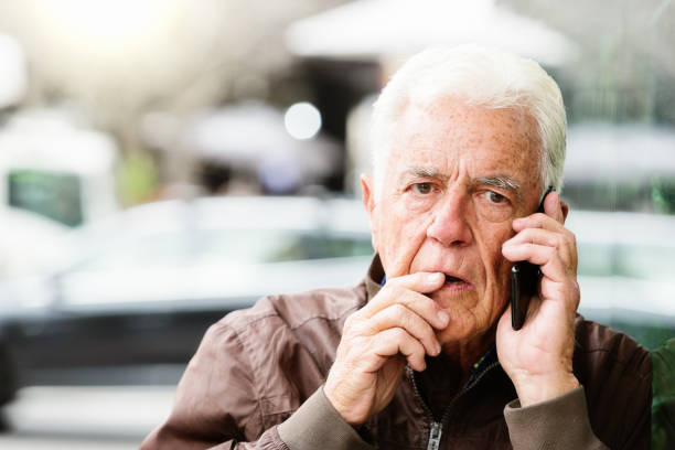 Senior man looks worried as he talks on his mobile phone in the street stock photo