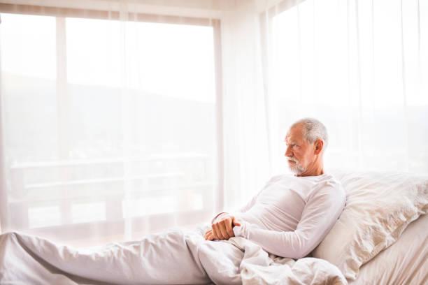 älteren mann im bett zu hause. - verstellbar stock-fotos und bilder