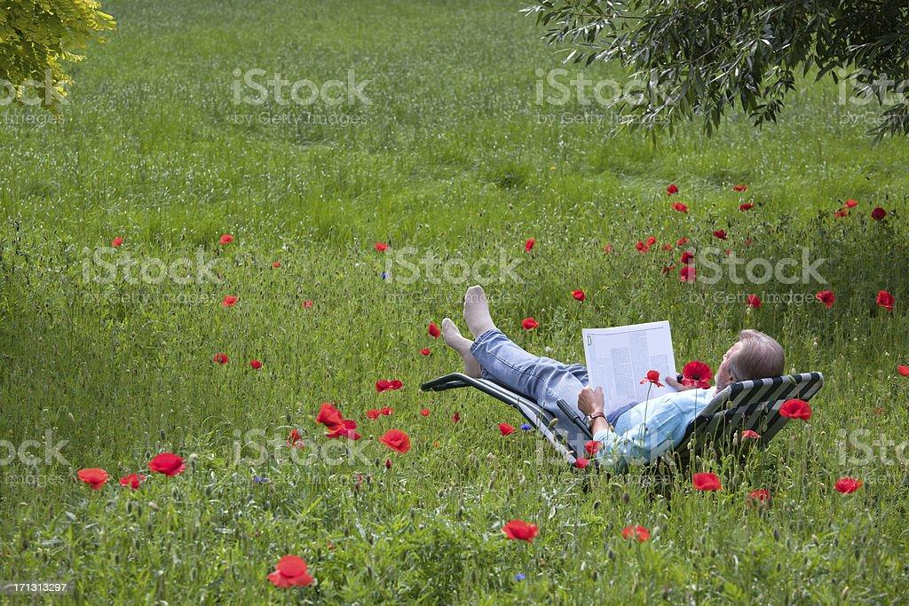 Senior man lying on deck chair in garden reading book royalty-free stock photo
