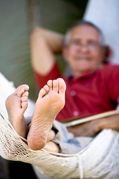 senior man lying on hammock focus feet - old man feet stock photos and pictures
