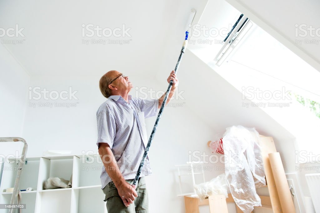 Senior man makes home improvement with new paint stock photo