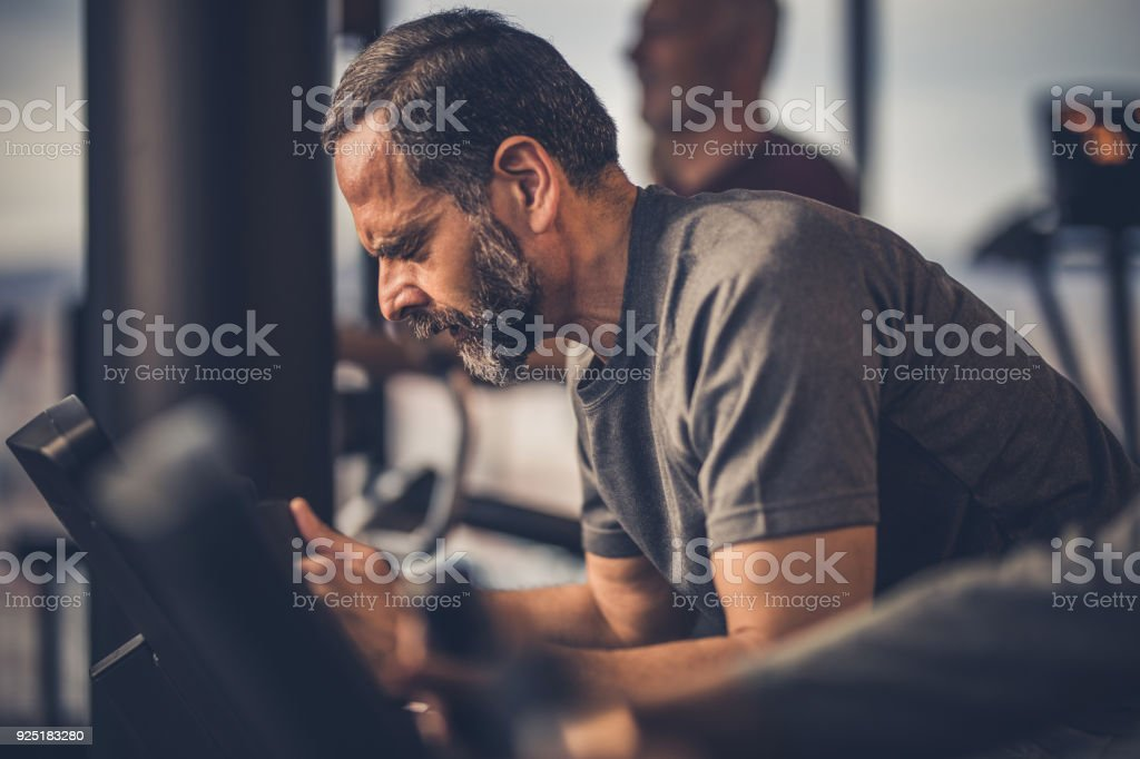 Mature man making an effort while riding an exercise bike with his...