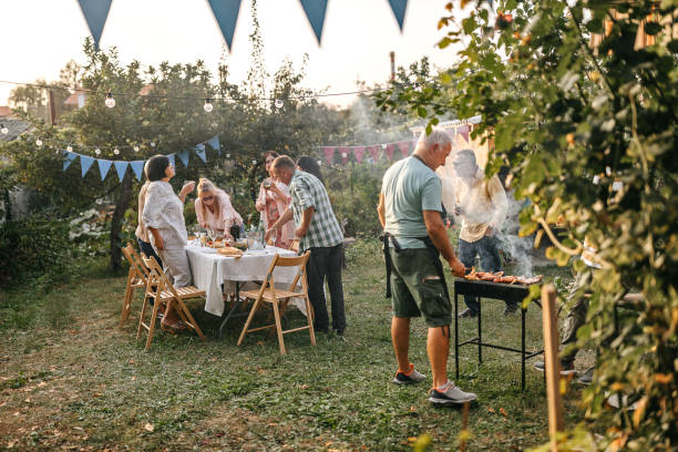 Senior man making barbeque for his friends during garden party stock photo