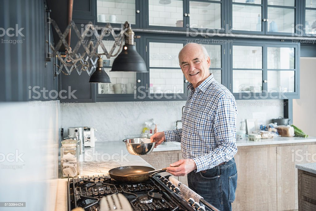Senior man making dinner and smiling to camera in kitchen stock photo