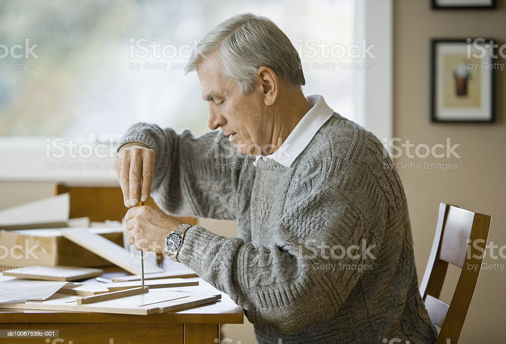 Senior man making household items, side view royalty-free stock photo