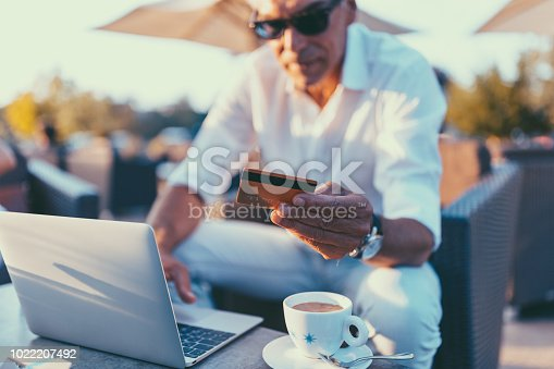 Man at cafe using credit card and laptop for online payments