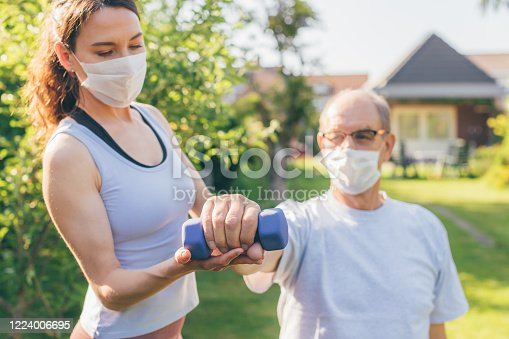 istock Senior man making physiotherapy session with young doctor (woman) 1224006695