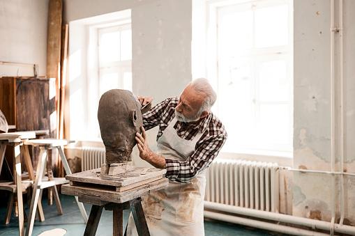 Senior man making statue of clay
