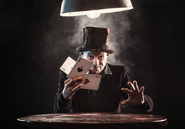 Senior man making trick with playing cards Senior man making trick with playing cards magician stock pictures, royalty-free photos & images