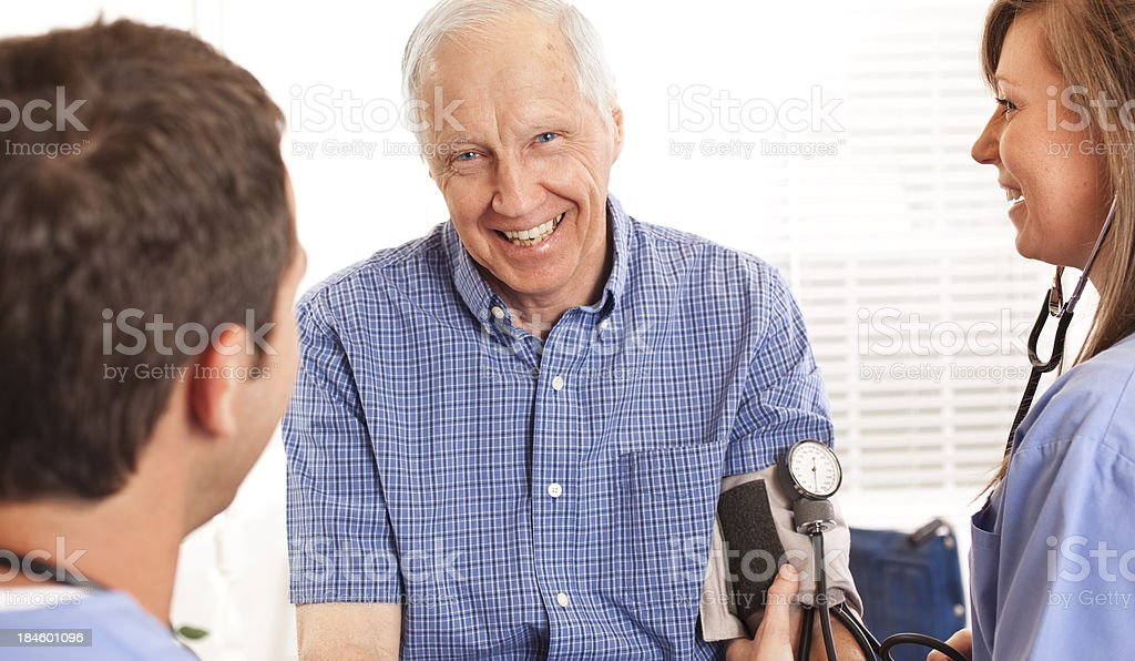 Senior man being checked by doctor, nurse checking blood pressure