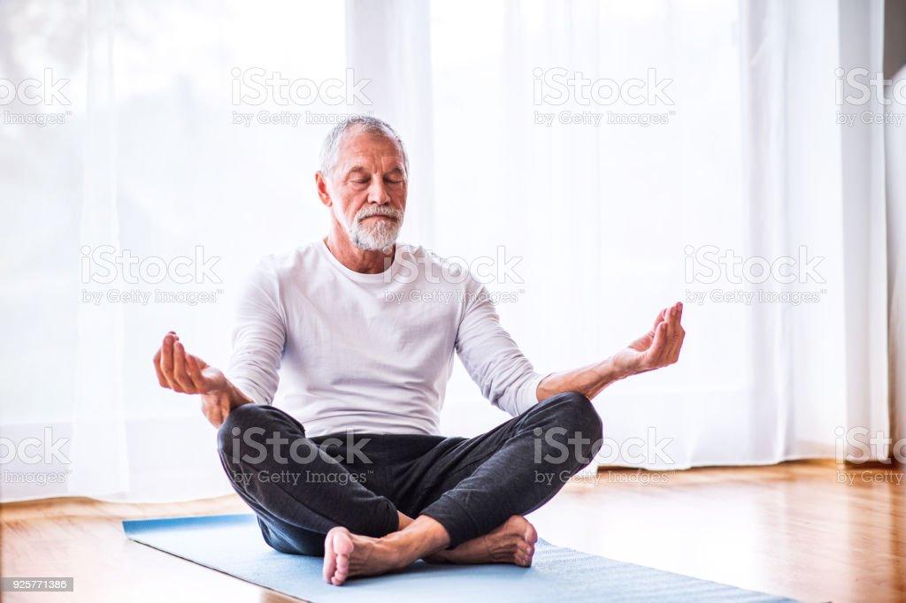 Senior man meditating at home. stock photo
