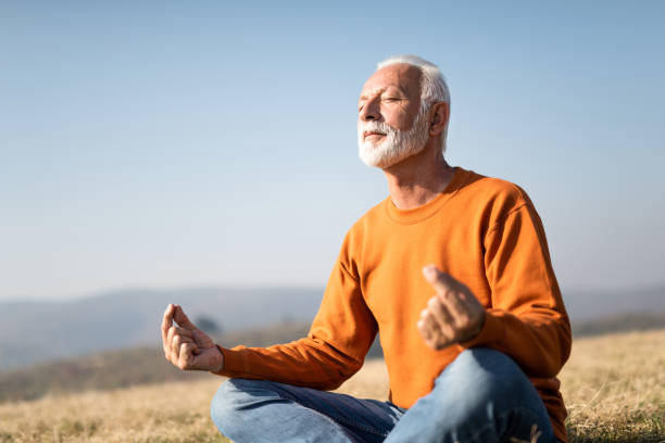 senior man meditating in nature. - meditation stock pictures, royalty-free photos & images