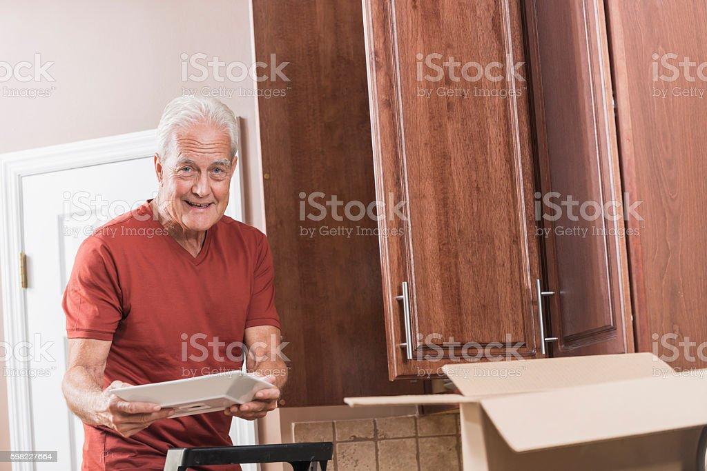 Senior man moving house, unpacking plates foto royalty-free