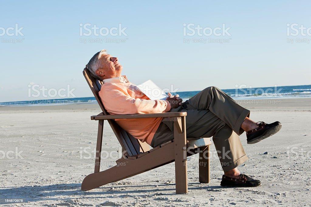 Senior man napping on beach stock photo