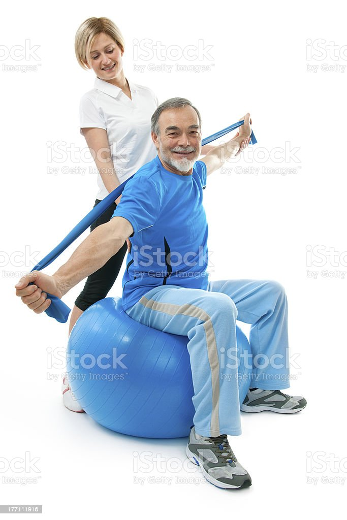 A senior man on a ball being trained royalty-free stock photo