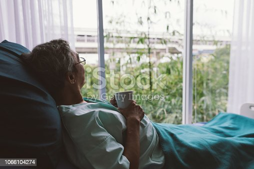 Senior man on a hospital bed alone in a room looking through the hospital window. Elderly patient