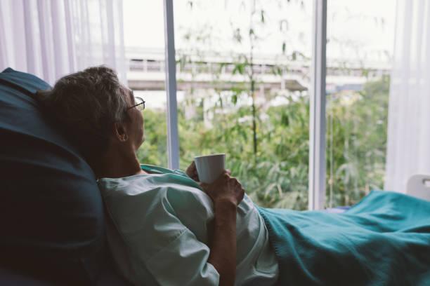 senior man op een ziekenhuisbed alleen op een kamer - raam bezoek stockfoto's en -beelden