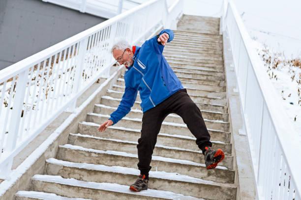 Senior man on a icy staircase falling Senior man on a icy staircase slippery stock pictures, royalty-free photos & images