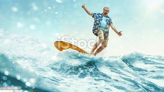 A senior man on a surfboard at blue sea