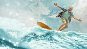 A senior man on a surfboard at blue sea. The summer, active, ocean, sea, surf, surfboard, surfer, adventure, beach, exercise, extreme, lifestyle, sport concept