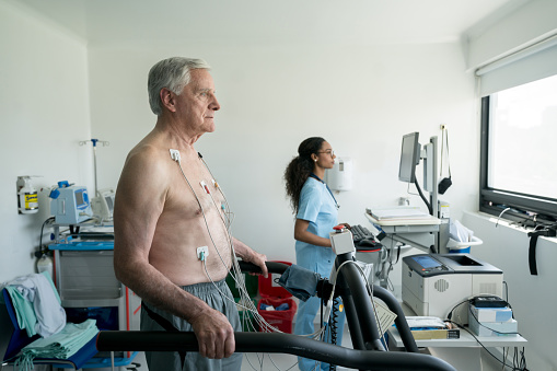 Senior man on a treadmill doing a stress test at the hospital while black nurse looks at the cardiac monitor very focused